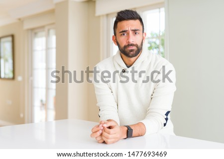 Handsome hispanic man wearing casual white sweater at home depressed and worry for distress, crying angry and afraid. Sad expression. #1477693469