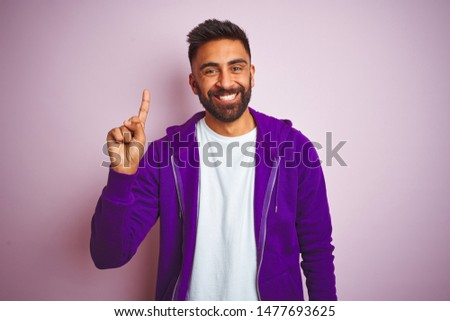Young indian man wearing purple sweatshirt standing over isolated pink background showing and pointing up with finger number one while smiling confident and happy. #1477693625