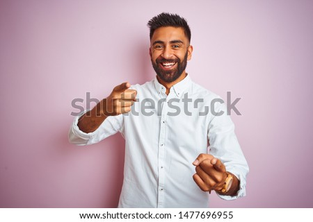 Young indian businessman wearing elegant shirt standing over isolated pink background pointing fingers to camera with happy and funny face. Good energy and vibes. #1477696955