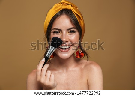 Close up beauty portrait of an attractive lovely young topless woman wearing headband standing isolated over brown background, holding makeup blusher brush #1477722992