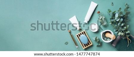 White cosmetic bottles, eucalyptus flowers, towels, soap on green background. Top view, flat lay. Natural organic beauty product concept. Spa, skin care, body treatment #1477747874