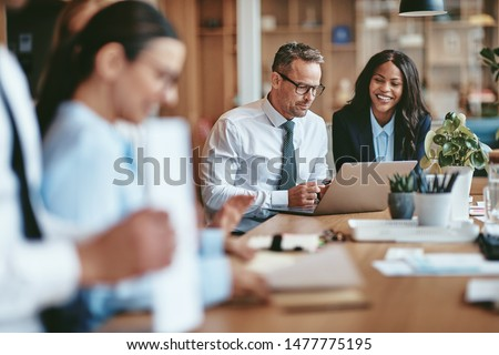 Two diverse businesspeople smiling while working on a laptop together at the end of a boardroom table in an office #1477775195