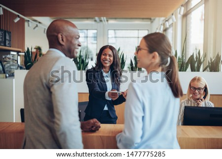 Friendly young African American concierge working at a reception counter giving room information to two guests checking into a hotel #1477775285