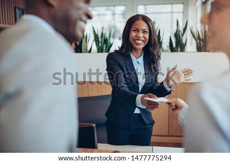 Friendly young African American concierge standing behind a reception counter giving room information to two guests checking into a hotel #1477775294