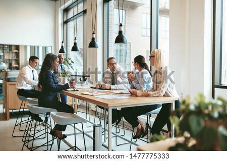 Diverse group of smiling businesspeople discussing paperwork together during a meeting around a table in a modern office #1477775333