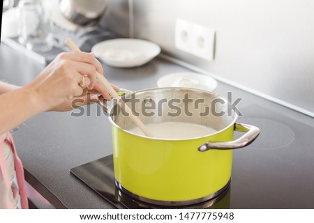 Woman preparing bechamel sauce or cream in a pan. Woman hand is mixing boiling milk with wooden spoon. #1477775948