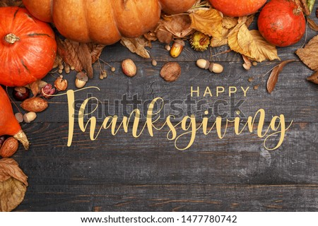 Thanksgiving Greetings. Pumpkins and dry leaves on a dark wooden background. Top view. Flat layer #1477780742