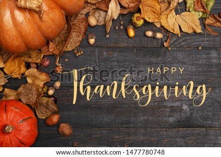 Thanksgiving Greetings. Pumpkins and dry leaves on a dark wooden background. Top view. Flat layer #1477780748