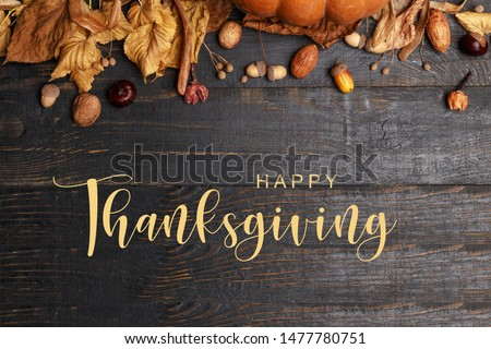 Thanksgiving Greetings. Pumpkins and dry leaves on a dark wooden background. Top view. Flat layer #1477780751