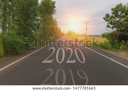 The word 2020 written on highway road in the middle of empty asphalt road at golden sunset and beautiful blue sky. Concept for new year 2020. #1477781663
