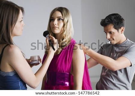 Designer and makeup artist preparing female model for photo shoot