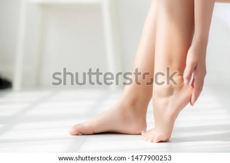 Closeup beautiful young asian woman applying cream and lotion onto foot dry on bed, beauty asia girl moisturizer and treatment cosmetic onto toes and heel, skincare cosmetic and healthy concept. Royalty-Free Stock Photo #1477900253