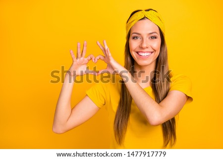 Portrait of lovely millennial making heart form with her hands smiling wearing t-shirt isolated over yellow background