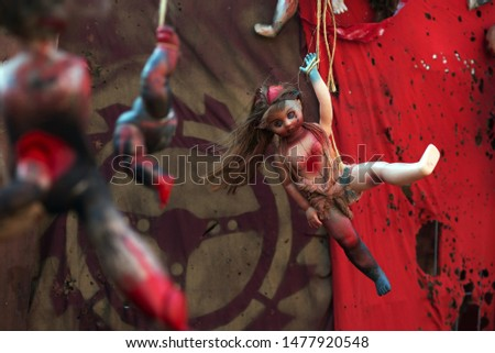 A doll in the style of post-apocalypse hangs on a rope against the background of ragged rags. #1477920548