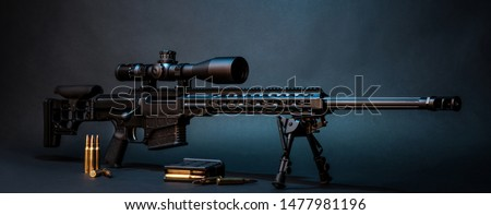 Modern powerful sniper rifle with a telescopic sight mounted on a bipod. Ammo and an additional magazine next to the rifle. #1477981196