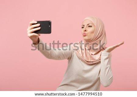 Pretty arabian muslim woman in hijab light clothes posing isolated on pink background. People religious lifestyle concept. Mock up copy space. Doing selfie shot on mobile phone, blowing send air kiss