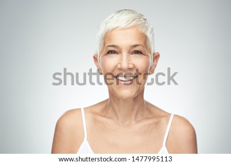 Beautiful smiling senior woman with short gray hair posing in front of gray background. Beauty photography. #1477995113