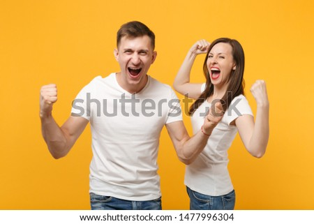 Joyful young couple friends guy girl in white empty blank t-shirts posing isolated on yellow orange background. People lifestyle concept. Mock up copy space. Clenching fists like winners, screaming #1477996304