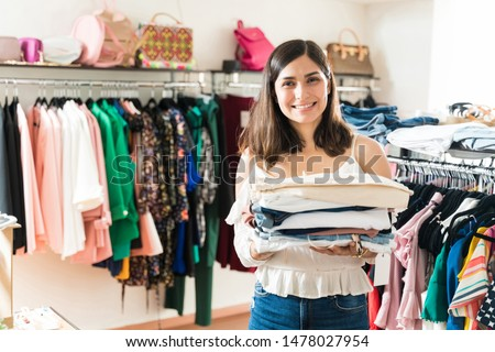 Pretty young female customer holding folded fashion apparels while making eye contact in clothing store #1478027954