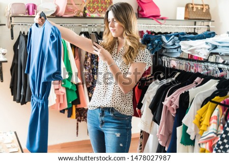 Beautiful young woman photographing top while standing against clothes rack in store at shopping mall