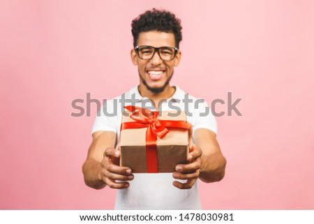 Cheerful smiling african american millennial guy in eyewear holding wrapped present box. Happy black young man congratulating, giving birthday gift, isolated on pink background.