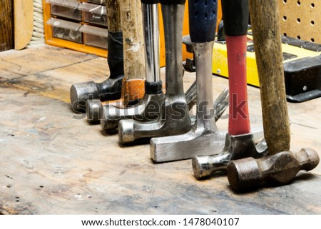 Row of hammers standing on their heads in a line; various shapes and sizes of hammer tools together in a line #1478040107