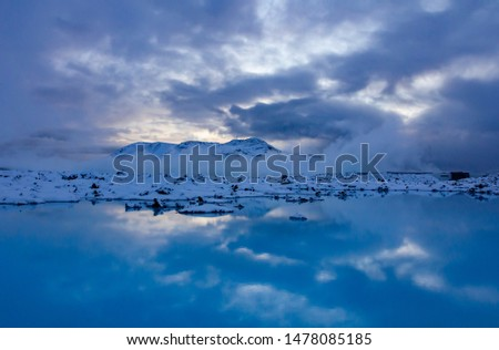 Blue lake in the midst of a lava field during snowy winter with reflection from the skies above #1478085185