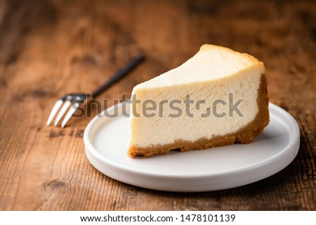 Cheesecake slice, New York style classical cheese cake on wooden background. Slice of tasty cake on white plate served with dessert fork #1478101139