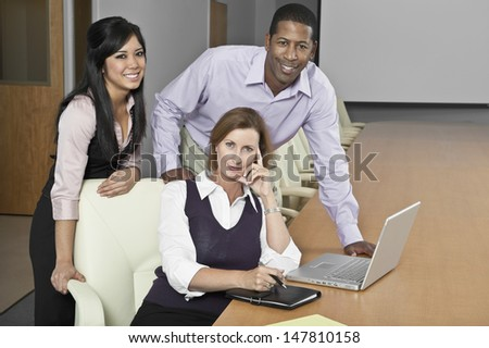 Portrait of smiling multiethnic businesspeople with laptop in conference room #147810158