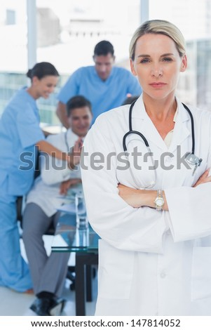 Serious blond doctor posing with colleagues in background in medical office #147814052