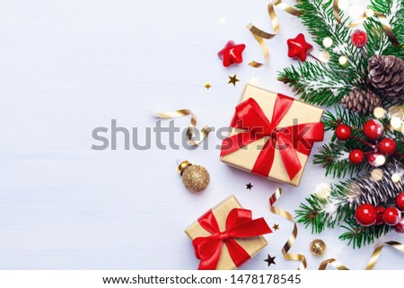 Beautiful Christmas composition on white background with golden Christmas gift boxes, snowy fir branches, conifer cones, holiday decoration and red berry. Top view. #1478178545