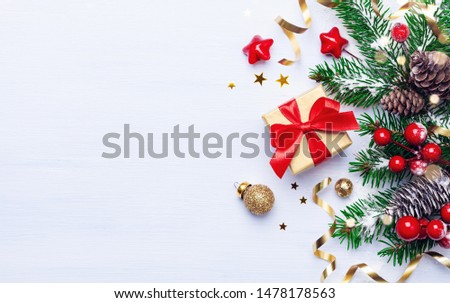 Christmas background with beautiful golden gift or present box, snowy fir branches, conifer cones, holiday decoration and red berry. Top view #1478178563