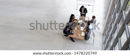 Top view of group of multiethnic busy people working in an office, Aerial view with businessman and businesswoman sitting around a conference table with blank copy space, Business meeting concept Royalty-Free Stock Photo #1478220749