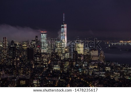 New York City skyline with lower Manhattan skyscrapers in storm at night.