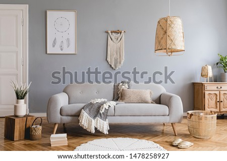 Design bohemian composition of living room interior with gray sofa, wooden cube, commode, beige macrame, rattan lamp ,plants, plaid, flowers and elegant accessories. Stylish home decor. Template. #1478258927