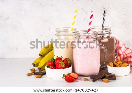 Set of milkshake in mason jars. Banana, chocolate and strawberry milkshakes. Summer dessert. Healthy food. #1478329427