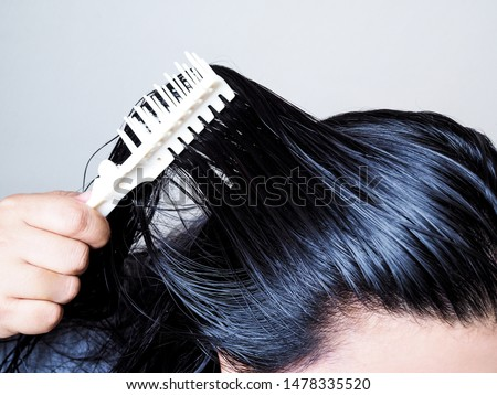 Close-up on head of Asian people have long black hair, combing hair with hairbrush. Black and thick hair health. #1478335520