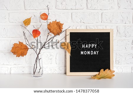 Happy Monday text on black letter board and bouquet of branches with yellow leaves on clothespins in vase on table Template for postcard, greeting card Concept Hello autumn Monday. #1478377058