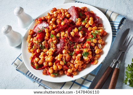 Garbanzos fritos, hot Chickpea stew with sliced chorizo, ham, tomatoes and spices on a white plate on a white concrete table, spanish cuisine, view from above, close-up #1478406110