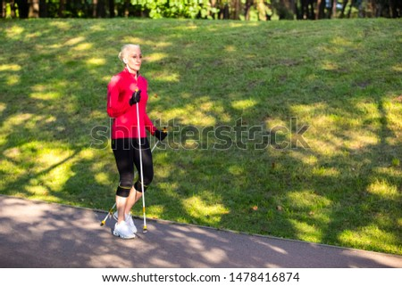 Full Length Portrait of Positive Sportive Senior Woman Doing Nordic Walking in Park. Horizontal image Composition #1478416874
