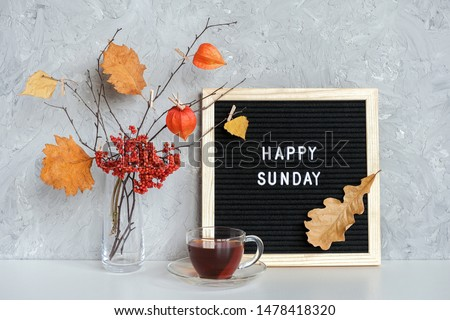 Happy Sunday text on black letter board and bouquet of branches with yellow leaves on clothespins in vase and cup of tea on table Template for postcard, greeting card Concept Hello autumn Sunday. #1478418320
