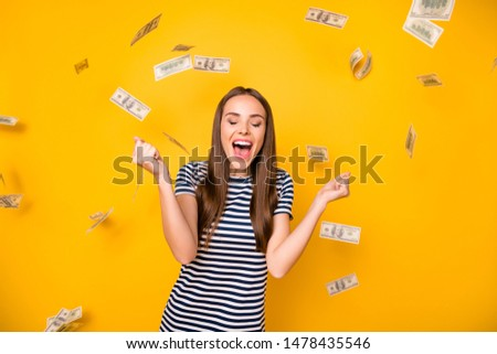 Pretty lady holding bucks bills flying everywhere wear striped white blue t-shirt isolated yellow background
