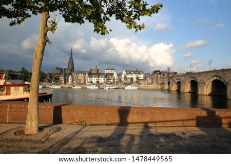 The Western banks of the Meuse river at sunset with Wyck neighborhood ( Sint Martinuskerk church) and  the 13th century roman bridge Sint Servaasbrug (on the right), Limbourg, Maastricht, Netherlands #1478449565