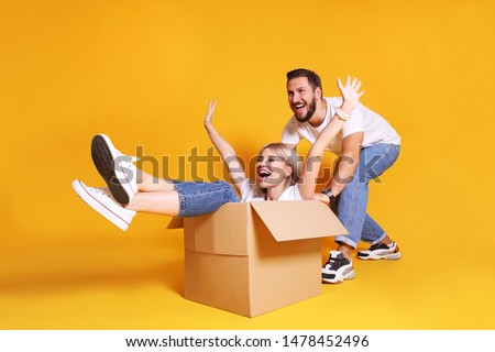 Young married couple moving into a new home. Attractive blonde woman sitting in cardboard box while bearded man pushes her. Newely weds fooling around. Isolated yellow background, copy space, close up #1478452496