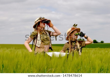 Two young girls dress up as explorers.They pose in  a prairie grassland countryside dressed with jungle  hats and khaki safari clothes. #1478478614