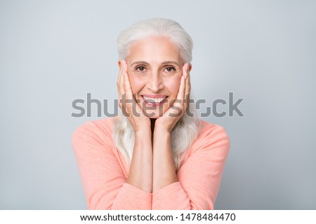 Photo portrait of attractive pretty glad calm peaceful old lady having charming toothy smile holding hands near head isolated grey background #1478484470