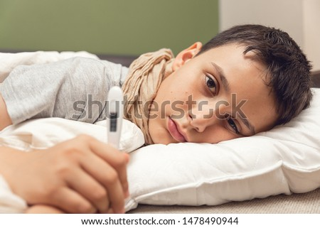 Sick boy with thermometer laying in bed. Sick child with fever and illness in bed. Flu. Cold #1478490944