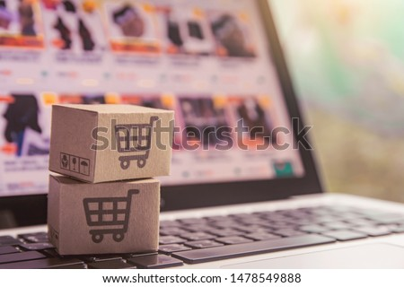 Online shopping - Paper cartons or parcel with a shopping cart logo on a laptop keyboard. Shopping service on The online web and offers home delivery. #1478549888