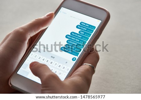 cropped view of abuser sending offensive messages while using smartphone, illustrative editorial #1478565977