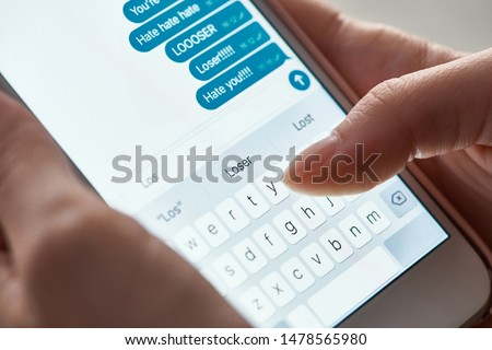 close up view of abuser sending offensive messages while using smartphone, illustrative editorial #1478565980